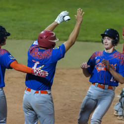 Holmes County's Derek Burke (right) is congratulated by teammates Braden Mast (left) and Mitch Massaro after scoring a run against Old Town during their Senior League World Series semifinal Thursday night at Mansfield Stadium in Bangor.