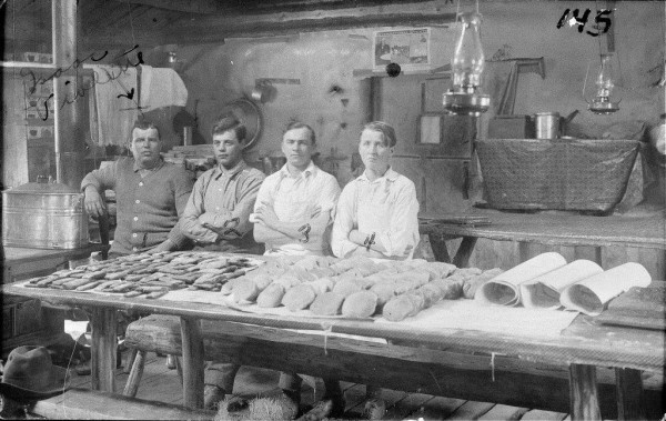 An undated photo shows a cook and his assistant &quotcookees&quot with their daily batch of bread and sweets.