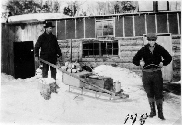Two men with a fully loaded &quotcookee's&quot one-runner sled in front of a camp building.