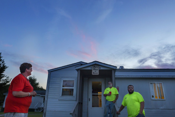 Melanie Morrell (left) jokes around with Brian Mulherin (center) and Joey Gilbert Jr. after dinner outside the dinning hall at Comstock Camp Tuesday.