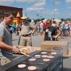 Marshall DesJardin of Winterport cooks hamburgers at the Hampden Recreation Department food booth set up next to the Weatherbee School for Hampden Children's Day festivities in 2013.