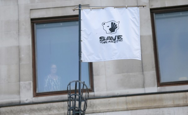 A woman looks out of a window of the Shell Building as a Greenpeace &quotSave the Arctic&quot flag flies outside in London, Sept. 28, 2015. Royal Dutch Shell has abandoned its Arctic search for oil after failing to find enough crude in a move that will appease environmental campaigners and shareholders who said its project was too expensive and risky.