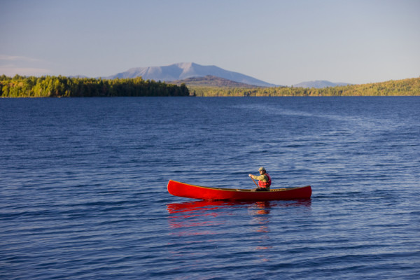 A canoeist enjoys paddling on Seboeis Lake, which is part of the Seboeis Public Reserved Lands Unit managed by the Maine Bureau of Parks and Lands, under the Maine Department of Conservation.