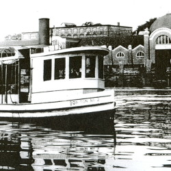"The little Bon Ton Ferry connected Bangor and Brewer across the Penobscot River for many years along the course followed by the Chamberlain Bridge today. In the background is the terminal operated by the Eastern Steamship Co. where the big ""Boston Boats"" arrived."