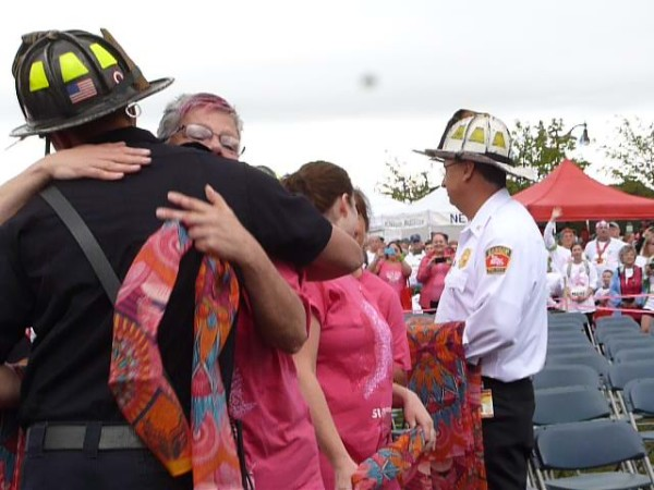 Bangor firefighters give out scarves and hugs to breast cancer survivors at the Susan G. Komen Race for the Cure on Sunday at the Bangor Waterfront.