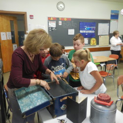 Fourth-grade students at Katahdin Elementary School examine an old trunk containing journals kept by Irene Olsen Bradford of Patten, which author Lynn Olsen Brown (left) used in writing a book about her aunt Irene's life on the farm. Brown contributed to the students' study of potato harvest with a presentation on Sept. 23.