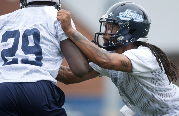 University of Maine football player  Sherrod Baltimore (right) runs through a drill during practice Aug. 21 at Alfond Stadium in Orono.