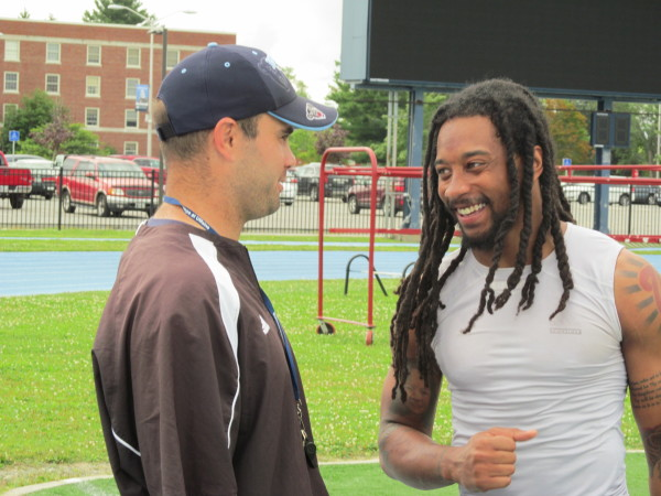 University of Maine senior cornerback Sherrod Baltimore (right) chats with defensive coordinator Joe Harasymiak after a recent practice at Morse Field in Orono.
