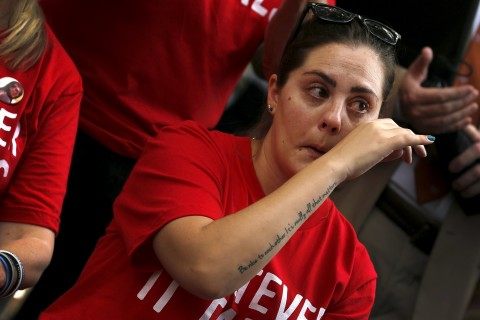 A woman wearing a tattoo of the quote &quotBe nice to each other. It's all that really matters,&quot attributed to slain Sandy Hook Elementary School Principal Dawn Hochsprung, wipes away tears at a rally against gun violence, on the U.S. Capitol grounds in Washington September 10, 2015.