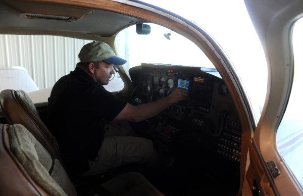 Gary Soucy, image specialist and pilot with Down East Emergency Medical Institute,  turns on the GPS in the cockpit of a late 1970s model Grumman Cougar twin engine plane that was donated to DEEMI by Doug Kell of Ellsworth.
