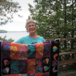 Marty Kelley displays quilt created by members of Voices for Peace, which she founded 10 years ago in Bangor. She will receive the Hands of Peace Award on October 3rd at the Peace and Justice Center of Eastern Maine's Harvest Supper.