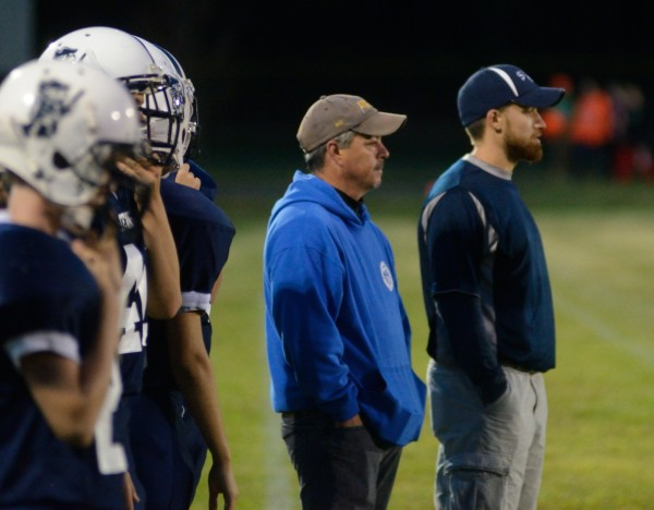 Stearns assistant football coaches Mark Boynton (center) and Josh Studer and a few players look on from the sidelines during a Sept. 11 game against Medomak Valley in Millinocket.