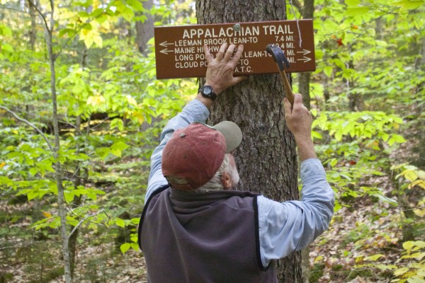 Ron Dobra, the Maine Appalachian Trail Club overseer for the Whitecap District of the Appalachian Trail, secures a new trail sign to a tree on Oct. 13, on the Appalachian Trail near the Wilson Valley shelter near Greenville. Dobra is one of many MATC volunteers who maintain the Appalachian Trail in Maine.