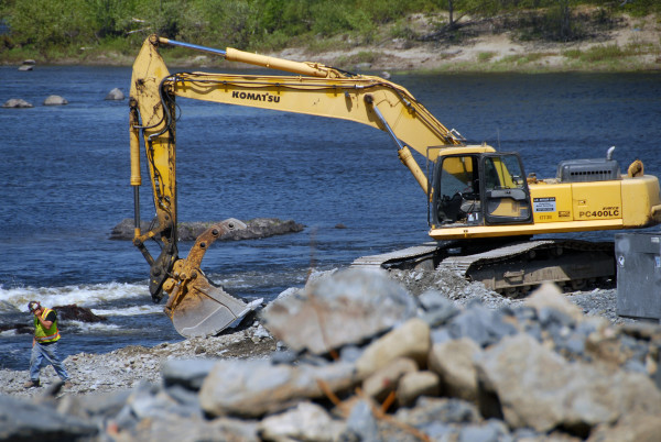 A backhoe operator takes a break from working on the Penobscot River Restoration Trust's fish bypass in Howland, May 27, 2015.