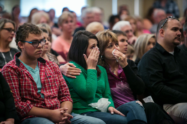 Lacey Scroggins, 18, center left, and her mother, Lisa Scroggins, center right, weep as they listen to Pastor Randy Scroggins talk about the recent Umpqua Community College mass shooting during a service at the New Beginnings Church of God in Roseburg, Oregon, Sunday, Oct. 4, 2015.
