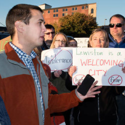 With his wife, Nicola (left), by his side, Lewiston mayoral candidate Ben Chin (second from left) addresses a crowd gathered along Main Street to denounce racism and hate Monday evening in Lewiston.