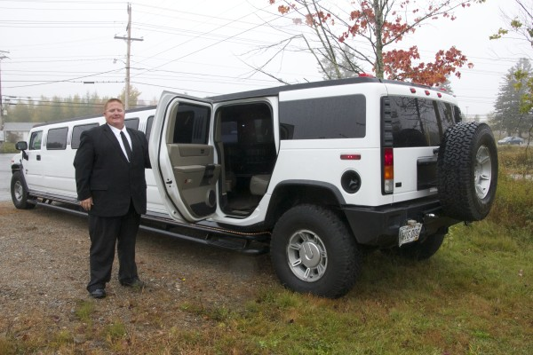 Dean McGuire holds open the door to his 2004 Hummer H2 limousine on Oct. 13 in Machias. His business is booming in Machias.
