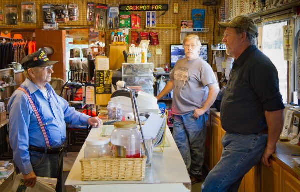 Shop co-owners Wayne Seidl (front right) and Joe Ruff (back right) talk with a customer at the Waite General Store. Residents of the small Washington County town of Waite, population 101, purchase more lottery tickets per capita than any other town in the state, according to lottery sales data.
