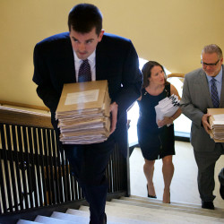 Lance Libby (from left), Adrienne Bennett and Peter Steele of the governor's office carry 65 veto letters up to the Legislature at the State House on July 16 in Augusta.
