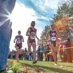 Orono's Olivia Fandel, George Stevens Academy's Zeya Lorio and Orono's Camille Kohtala pass spectators just past the two-mile point of Saturday's Class C state championship cross country meet at Twin Brook Recreation Area in Cumberland. Orono went on to win the team title.