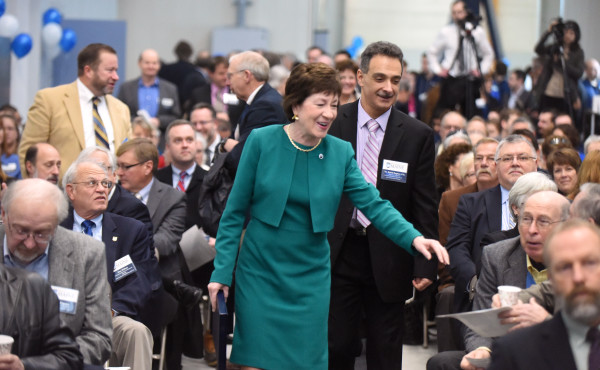 Sen. Susan Collins (center left) and Habib Dagher (center right), director of the Advanced Structures and Composites Center, walk to the podium before a ceremony to unveil a new facility at the University of Maine on Monday in Orono. The facility will allow the testing of designs for offshore floating wind turbines, underwater turbines and ships in various wave and wind conditions.