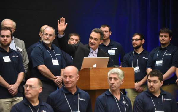 Habib Dagher (center), director of the Advanced Structures and Composites Center, talks during a ceremony to unveil a new facility at the University of Maine on Monday in Orono. The new laboratory will allow the testing of designs for offshore floating wind turbines, underwater turbines and ships in various wave and wind conditions.