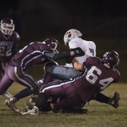 Mattanawcook Academy player Carter Ward (7) is sacked by MCI players Aaron Noonan (5) and Curtis McLeod (64) in the first half of their game in Pittsfield on Friday.