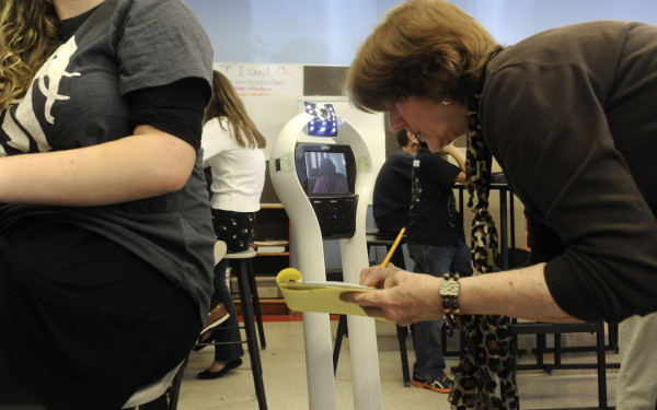Camden-Rockport Middle School math teacher Donna Peterson gets up close to Katherine's VGo robot to hear her ask a question during class recently.