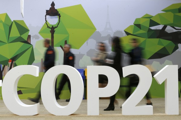 People walk walks past the COP21 logo in the Climate Generations area during the World Climate Change Conference 2015 at Le Bourget, near Paris, France, Dec. 1, 2015.