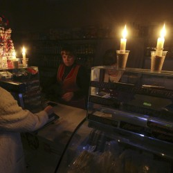 A customer visits a grocery lit with candles due to a power cut, in Simferopol, Crimea, in this Nov. 22, 2015, file photo.