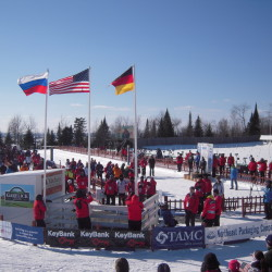 Volunteers in red jackets on the shooting range for the 2014 Youth/Junior International Biathlon Union World Championships at the Nordic Heritage Center in Presque Isle had designated roles, which included raising the national flags of biathletes in the first three places of each race.