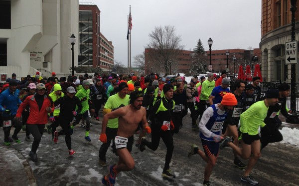 Matthew Adams (without shirt) leads the pack of runners at the start of the 10th annual Epic 5K Finale on Sunday morning at West Market Square in Bangor. Adams, who is from Seward, Alaska, went on to win the race with a time of 15 minutes, 47 seconds.
