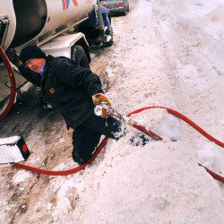 Greg Hamilton, a delivery driver with Dead River Co., struggles through a waist-high snowbank after filling the oil tank at a Brewer home in 2013.