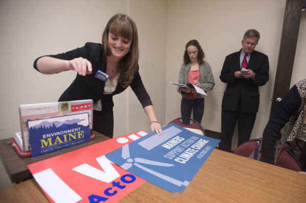 Laura Dorle (left), the campaign organizer with Environment Maine, arranges signs before a press conference at the Bangor City Hall Thursday afternoon. They talked about a new report detailing the wind energy potential and progress in the state. Also pictured are speakers Wells Mundell-Wood and Bangor City Council chairman Sean Faircloth.