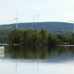 Turbines from SunEdison Inc.'s wind project in Oakfield can be seen from the public landing of Drew's Lake in New Limerick.