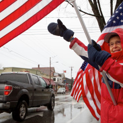 Freeport flag lady Carmen Footer waves to a honking truck Tuesday morning on Main Street. The flag ladies have been waving the Stars and Stripes on Main Street every Tuesday morning since Sept. 11, 2001.