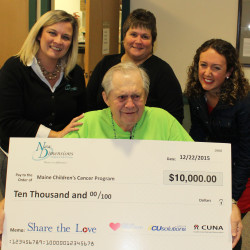 (L-R) Tina Morrill and Sharon Storti of New Dimensions FCU, and Tara Studley of the Maine Children's Cancer Program with Sylvio Normandeau, who has been a tireless fundraiser for the Maine Children's Cancer Program.  Normandeau is holding a $10,000 check the credit union received for a charity for winning a national, video contest.  The credit union donated the $10,000 to the Maine Children's Cancer Program on behalf of Normandeau and his quest to raise $500,000 for the Program.  The contribution brings Normandeau's all-time fundraising total to $468,000.