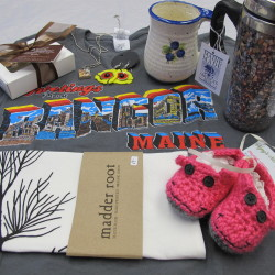 A small selection of items under $20 made in the Bangor area, including (clockwise from top left) Savour Chocolatier chocolates, earrings from Char Chiarito designs, Blueberry Ware mugs, Maine Shellware travel mugs, NyNy's Nest baby booties, Madder Root tea towels and Greetings from Bangor Maine gear.