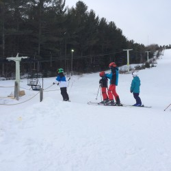 Skiers and snowboarders wait to get on the chair lift at Hermon Mountain Ski Area.