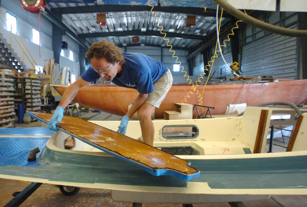A Morris Yachts employee works on the deck of an M29 Daysailer at Morris Yachts in Trenton in 2010. Hinckley Yachts announced Tuesday that it has acquired the smaller sailing yacht manufacturing firm.