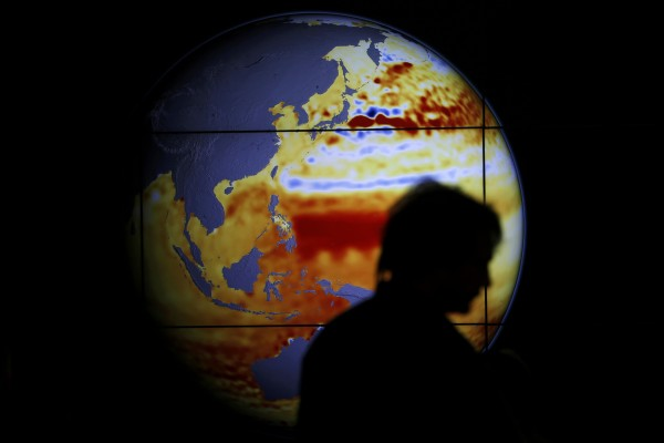 A woman walks past a map showing the elevation of the sea in the last 22 years during the World Climate Change Conference 2015 (COP21) at Le Bourget, near Paris, France, December 11, 2015.