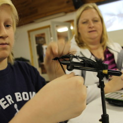 Noah Tibbetts, 11, of Brewer ties a fly while his mother, Julie Tibbetts, looks on during a session of the Penobscot Fly Fishers' introductory fly tying class in Brewer on Jan. 11, 2016.