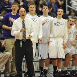 Hampden assistant coach Gary Colson (seated on left), head coach Russ Bartlett and members of the Broncos basketball team on the sidelines react to a team point during their Class A quarterfinal against Lewiston at the Augusta Civic Center in 2011.