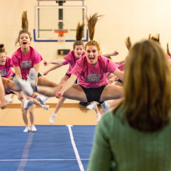 Hermon High School cheerleaders Cammie Peirce (left), Nicole Petersen (center) and Karissa Hatchermon (right) run through their routine with other teammates as coach Kristie Reed watches during a brief warm-up on Wednesday night in Hermon.