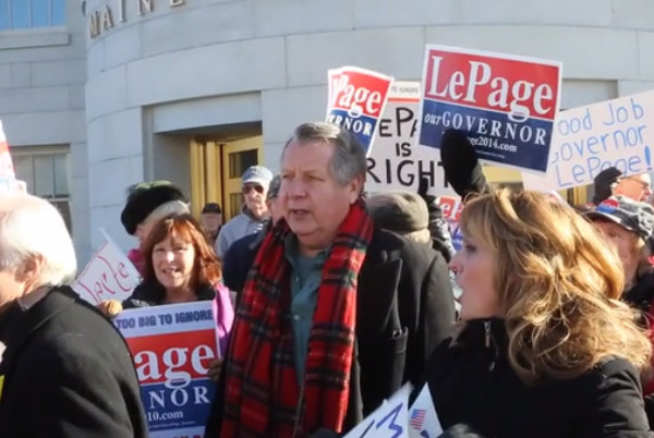 People hold signs at a rally in support of Gov. Paul LePage on Wednesday outside the State House in Augusta.