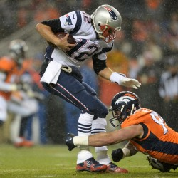 New England Patriots quarterback Tom Brady (12) is sacked by Denver Broncos defensive end Derek Wolfe (95) in the second quarter at Sports Authority Field at Mile High.