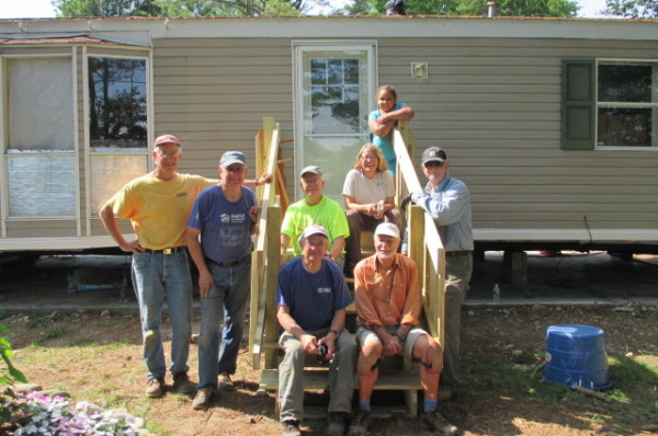 Members of the 7 Rivers Regulars, a community-based volunteer group that provides free home weatherization and safety improvements, pose at a job site near Bath.