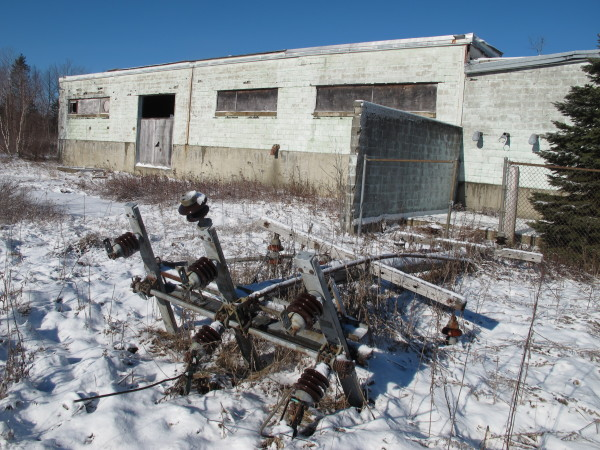 A broken electrical pole lies on the ground outside an old tannery near Route 1 in Hancock. Town officials are applying for $400,000 in federal brownfields grant money to help clean up 14 acres of the 150-acre property, including the decrepit building.