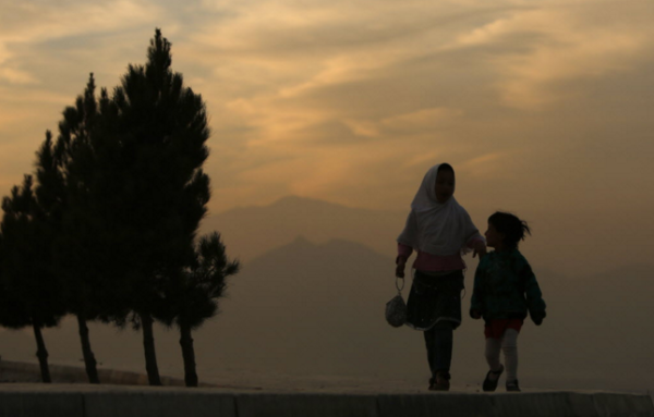 Children walk as the sun sets in Kabul city December 9, 2012.