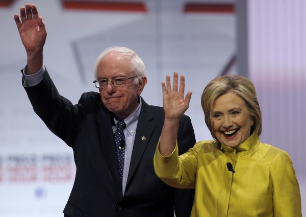 Democratic U.S. presidential candidates Sen. Bernie Sanders and former Secretary of State Hillary Clinton wave as they arrive on stage before of the start of the PBS NewsHour Democratic presidential candidates debate in Milwaukee, Wisconsin, Feb. 11, 2016.